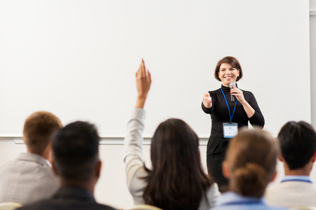 business, education and people concept - smiling businesswoman or teacher with microphone answering questions at conference presentation or lecture