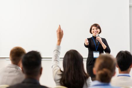 Geschäft, Bildung und Leutekonzept - lächelnde Geschäftsfrau oder Lehrer mit antwortenden Fragen des Mikrofons an der Konferenzdarstellung oder am Vortrag Standard-Bild