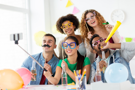 corporate, celebration and holidays concept - happy friends or team with party accessories taking selfie at office Stock Photo