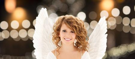 Femme heureuse avec des ailes d & # 39 ; ange sur les lumières de noël Banque d'images - 86414350