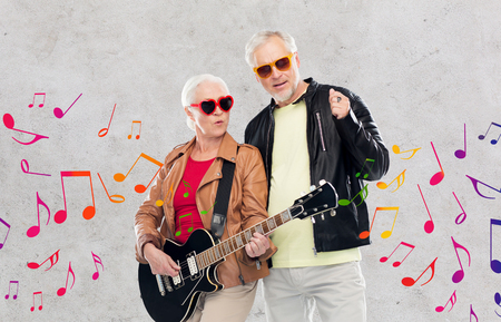 senior couple in sunglasses with electric guitar