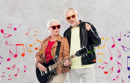 senior paar in zonnebril met elektrische gitaar