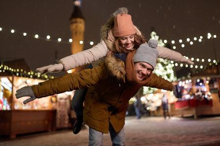 クリスマス マーケットで楽しんで幸せなカップル