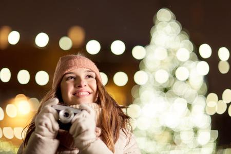 クリスマス ツリーをカメラで幸せな若い女
