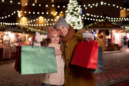happy couple at with shopping bags in winter