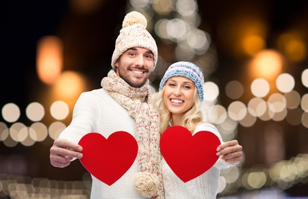 couple with red hearts over christmas lights