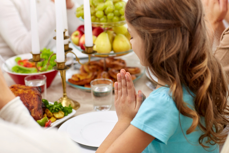 girl with family having dinner and praying at home