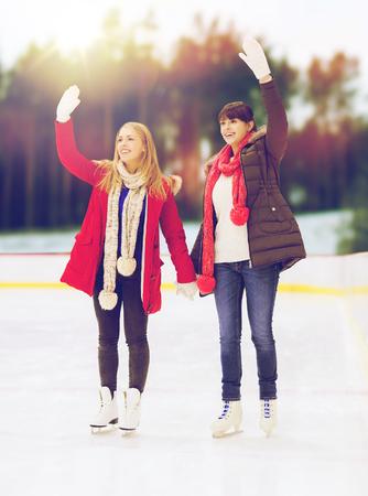 iceskates: women or friends waving hands on skating rink