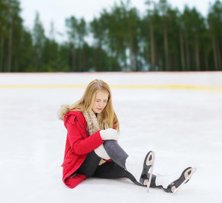 Mujer joven con lesión de rodilla en la pista de patinaje Foto de archivo - 86732754