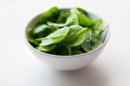close up of spinach leaves in white bowl