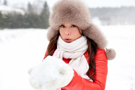 happy woman with snow in winter fur hat outdoors Stock fotó