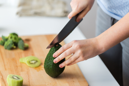 woman hands chopping avocado on cutting board