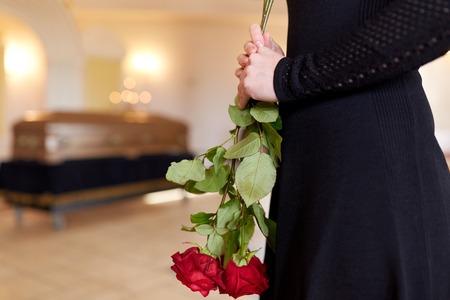 close-up van de vrouw met rozen en kist op de begrafenis Stockfoto