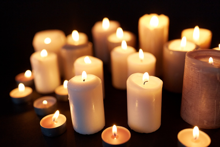 candles burning in darkness over black background Stock Photo