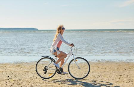 夏のビーチに沿って幸せな女乗って自転車