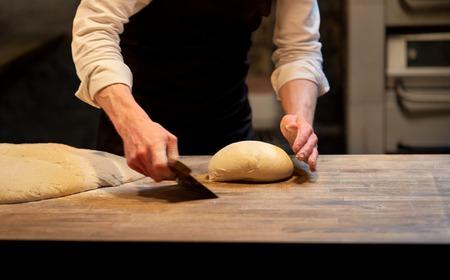 bakker portierdeeg met banksnijder in bakkerij Stockfoto