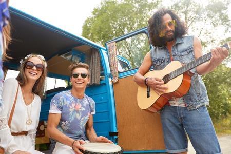 Gelukkige hippievrienden spelen muziek in minivan Stockfoto