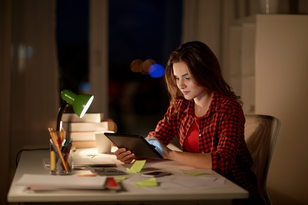 student girl or woman with tablet pc at night home Stock Photo