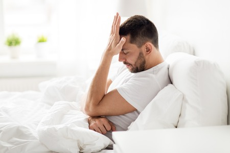 stressed man in bed at home