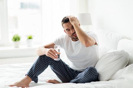 家庭での水のガラスが付いているベッドで男