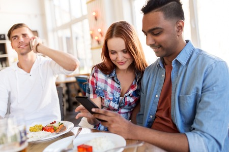 happy friends with smartphone at restaurant
