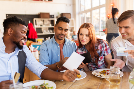 leisure, payment and people concept - happy friends with money and credit card paying bill for food at restaurant