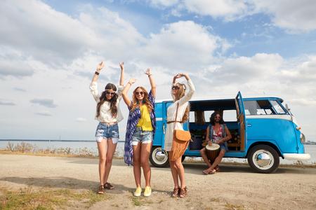 smiling hippie friends having fun near minivan car