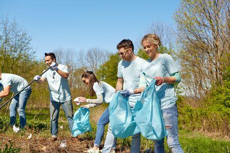 ボランティア、慈善団体、人々、エコロジー コンセプト - 幸せなゴミ袋公園地区の清掃ボランティアのグループ 写真素材