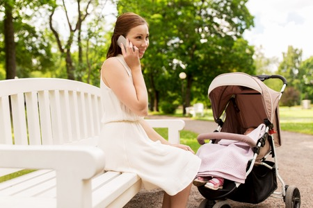 mother with stroller calling on smartphone at park Stock Photo - 86846898