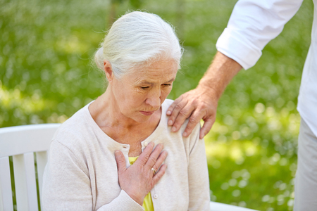 old age, health problem and people concept - senior woman feeling sick at summer park Stock Photo