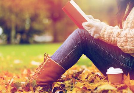 가을 공원에서 커피를 마시는 책을 가진 여자 스톡 콘텐츠