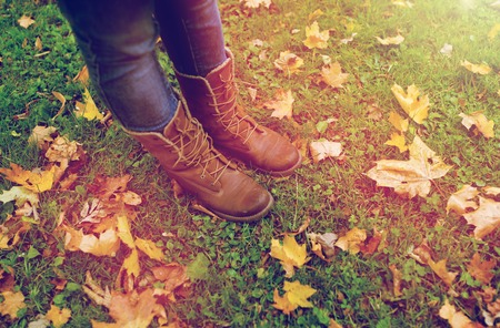 female feet in boots and autumn leaves on grass