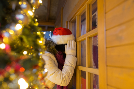 woman looking to house window at christmas market