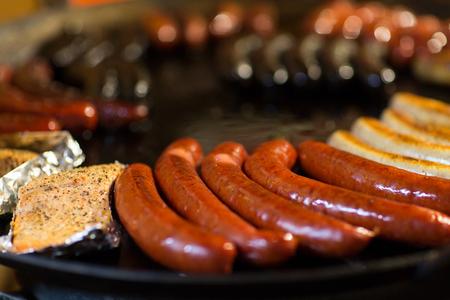roasting pan: sausages and salmon frying in stir fry pan Stock Photo
