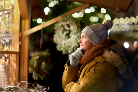 gelukkige mens die het venster van de Kerstmismarkt bekijken