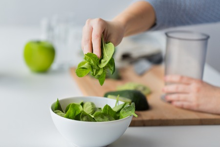 measuring cup: close up of woman hand adding spinach to bowl
