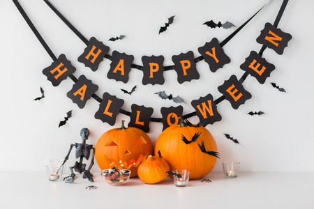 gesneden pompoenen met snoepjes en Halloween-slinger Stockfoto