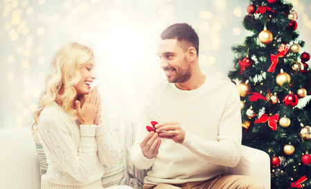 man giving woman engagement ring for christmas