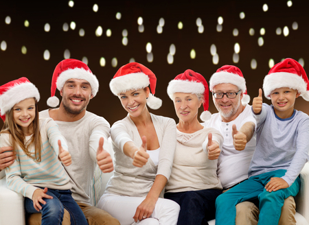 three generations: family in christmas santa hats showing thumbs Stock Photo
