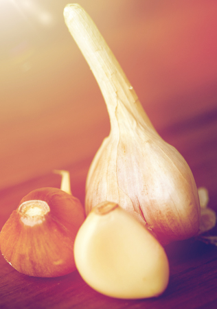 health, food, cooking, traditional medicine and ethnoscience concept - close up of garlic on wooden table