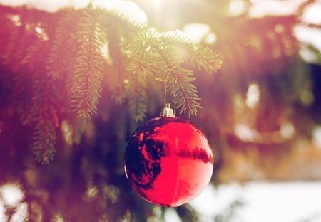 겨울 휴가 및 장식 개념 - 전나무 나뭇 가지에 빨간 크리스마스 공 눈으로 덮여