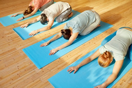 fitness, sport and healthy lifestyle concept - group of people with personal trainer doing yoga exercises on mats in gym or studio Stock Photo - 87213259