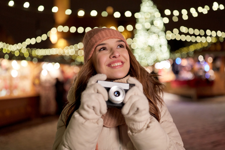 holidays, photography and people concept - beautiful happy young woman with camera at christmas market in winter evening 版權商用圖片
