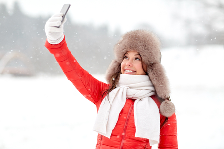 people, technology and leisure concept - happy woman in winter fur hat taking selfie by smartphone outdoors