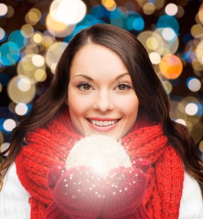 holidays, christmas and people concept - happy woman in scarf and mittens with magic ball over lights background