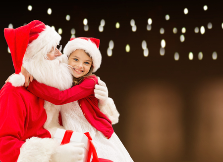 holidays, christmas and people concept - santa claus with gift and happy girl over lights background