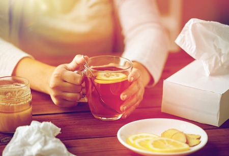 health, traditional medicine and ethnoscience concept - close up of ill woman drinking tea with lemon, honey and ginger at wooden table Lizenzfreie Bilder