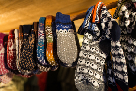 knitwear and winter clothes concept - woolen mittens at christmas market