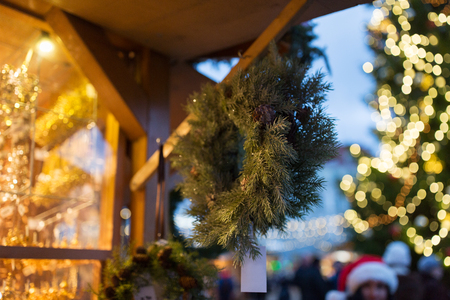 holidays and decoration concept - close up of fir tree wreath at christmas market canopy Stock Photo