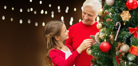 holidays, family and people concept - happy grandmother and granddaughter decorating christmas tree over lights background Lizenzfreie Bilder